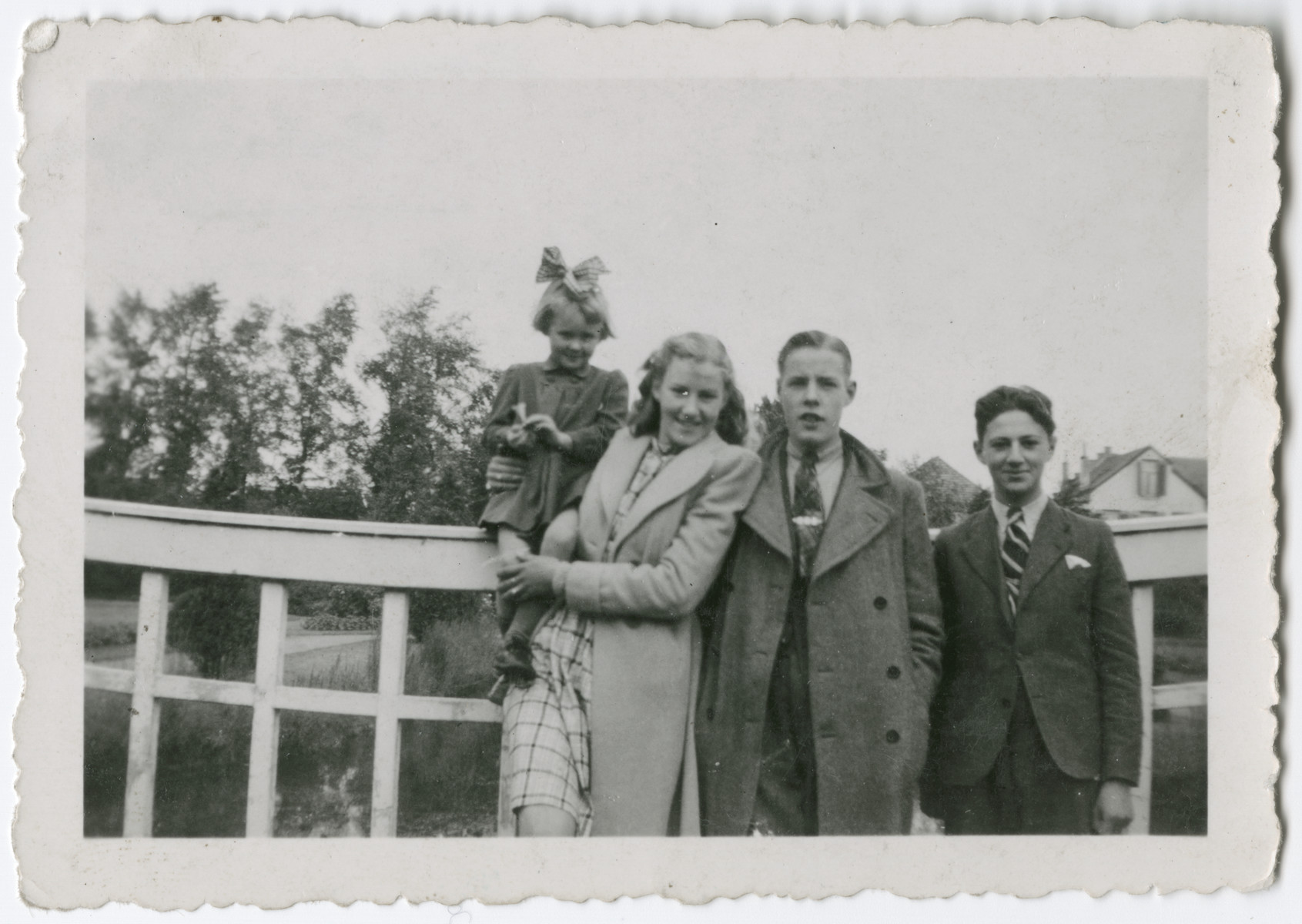 A rescued Jewish child poses with the children of rescuers.  Pictured are Feikje Bosman holding Bonnette Onderweegs, Feikje's boyfriend Roelof vander Veen, and Louis der Groot.  Bonnette is the daughter of resistance members Anne and Dick Onderweegs.  The Onderweegs had hidden Louis de Groot, and later went into hiding with the Bosman family after they were denounced for hiding Jews.