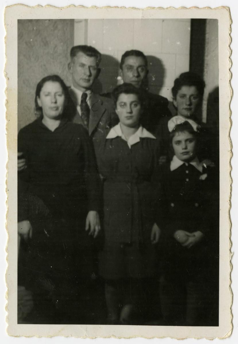 Family portrait of Jewish survivors in Lodz after the war.   First row (L-R): Abraham Murik and Elias Dawidowicz. Second row (L-R) Taube Dawidowicz, Ida Dawidowicz, Lisa Murik, and Chana Dawidowicz.
