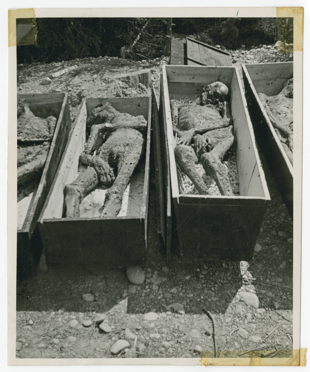 Bodies dug up from a mass grave lie in coffins prior to reburial.