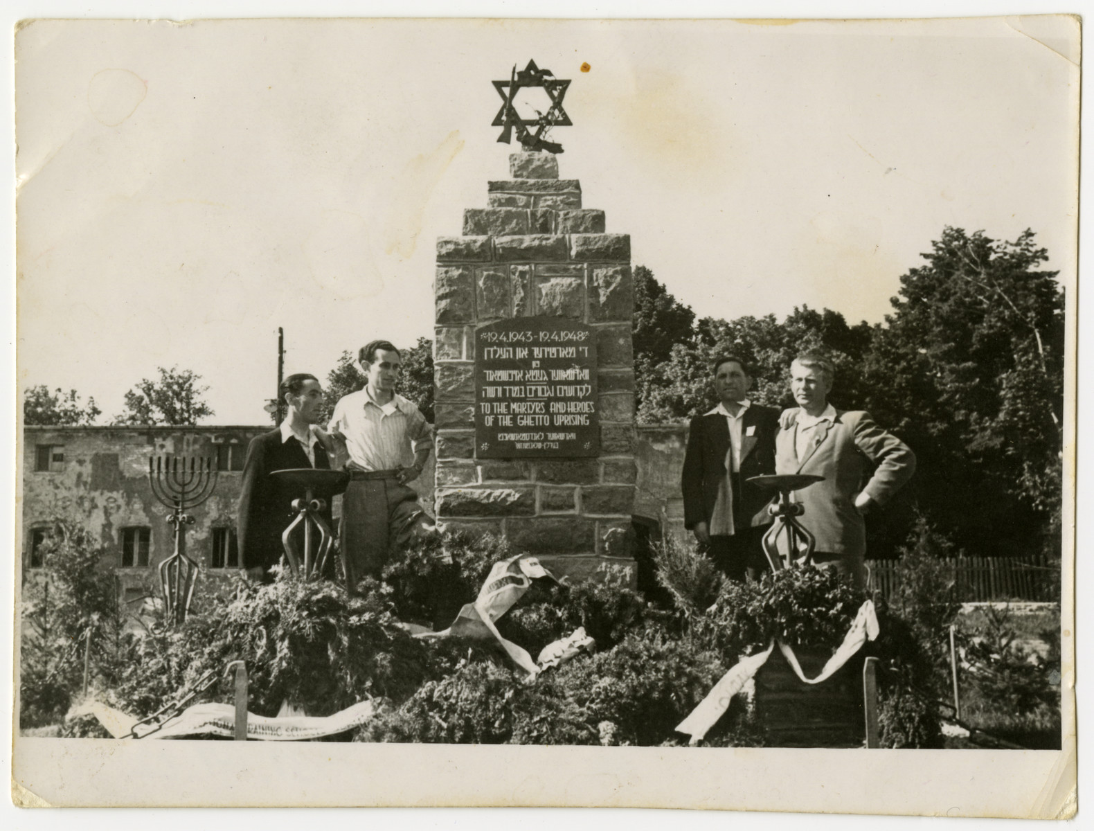 Four men pose next to a memorial marking the fifth anniversary of the Warsaw ghetto uprising probably in the Schlachtensee displaced persons camp.