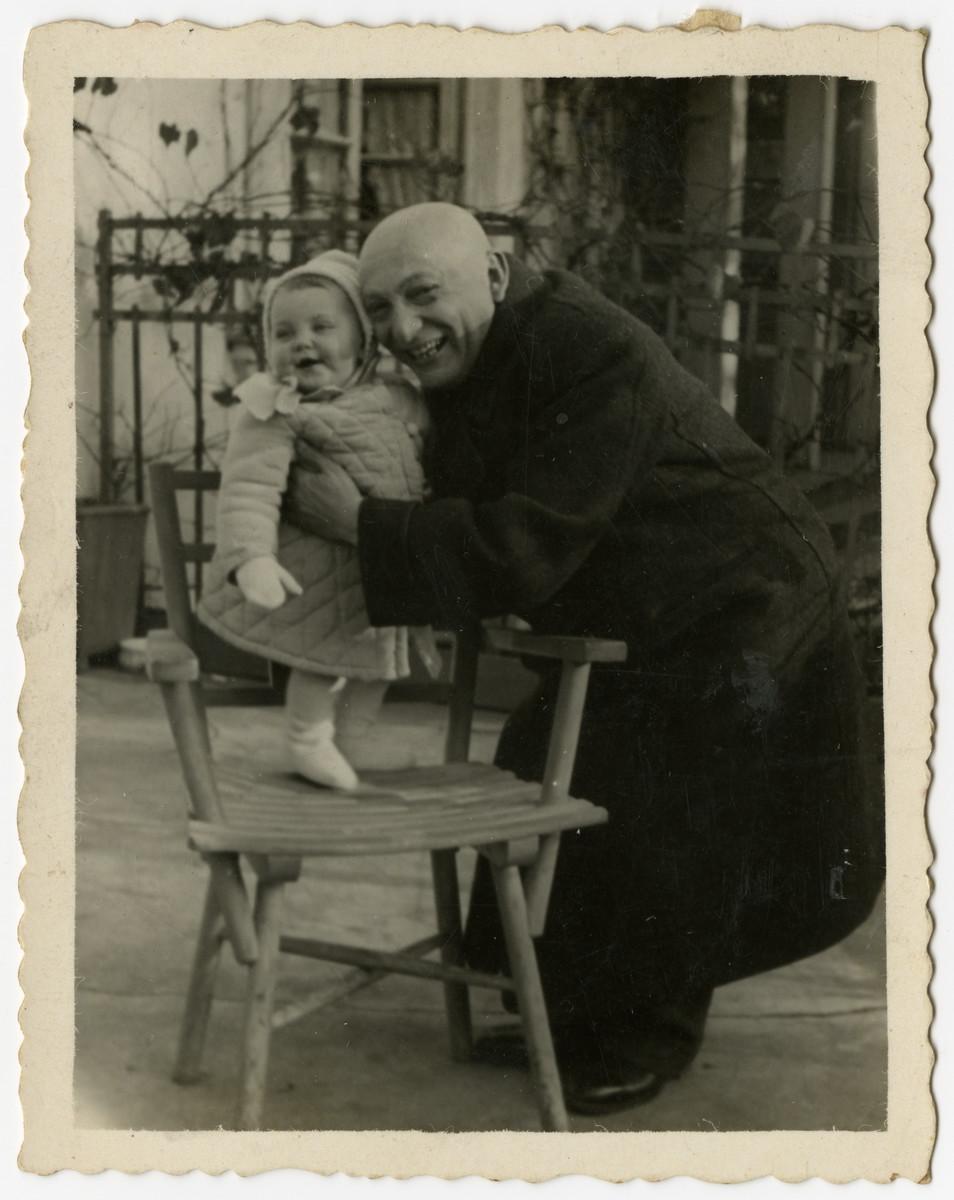 Benjamin Szymin hugs his baby granddaughter Helen.