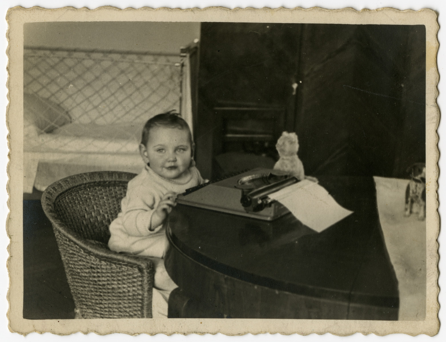 One-year-old Helen Sznajderman sits by a typewriter.
