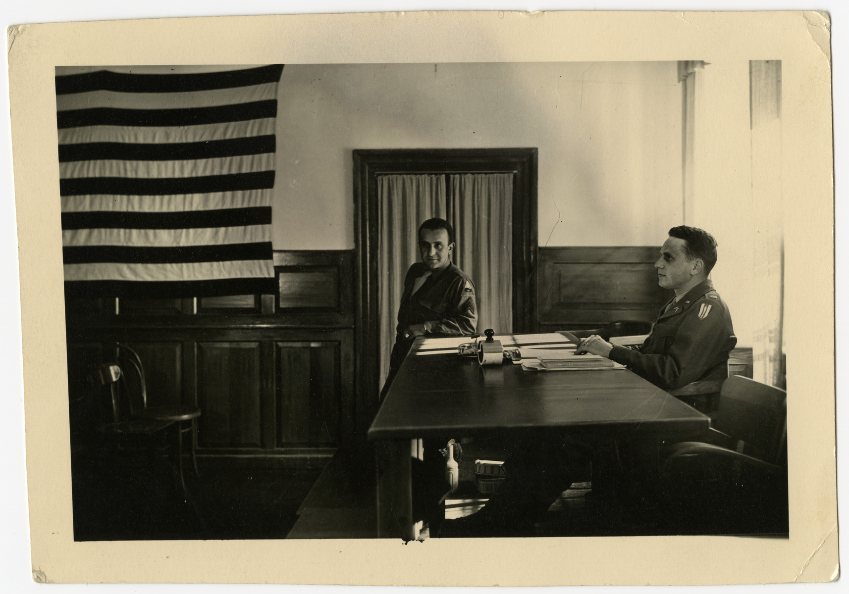 Jacob Postman, a Viennese Jewish emigre, serves as a  translator for the U.S. Army in an unidentified war crimes trial.    Jacob Postman is standing and Lt. Lizer is sitting at the desk.