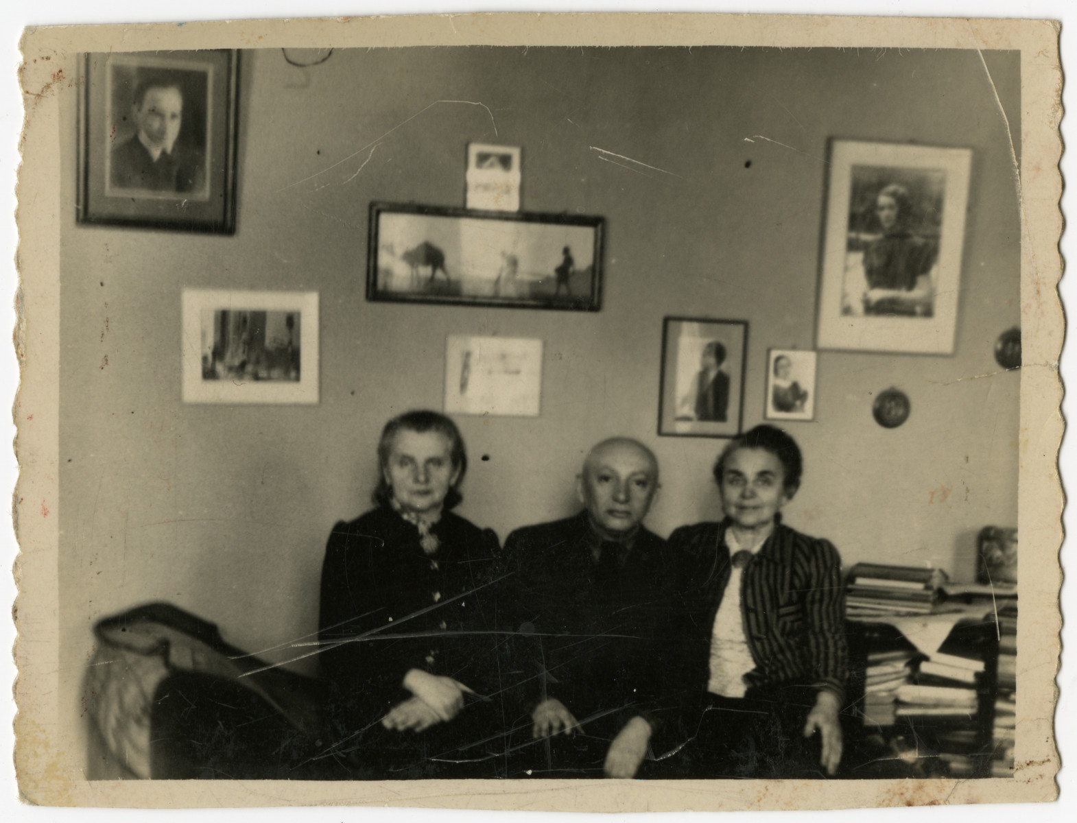Three elderly Jews pose in their apartment in the Otwock ghetto.  From left to right are Regina and Benjamin Szymin and Regina's sister, Malka Flint.