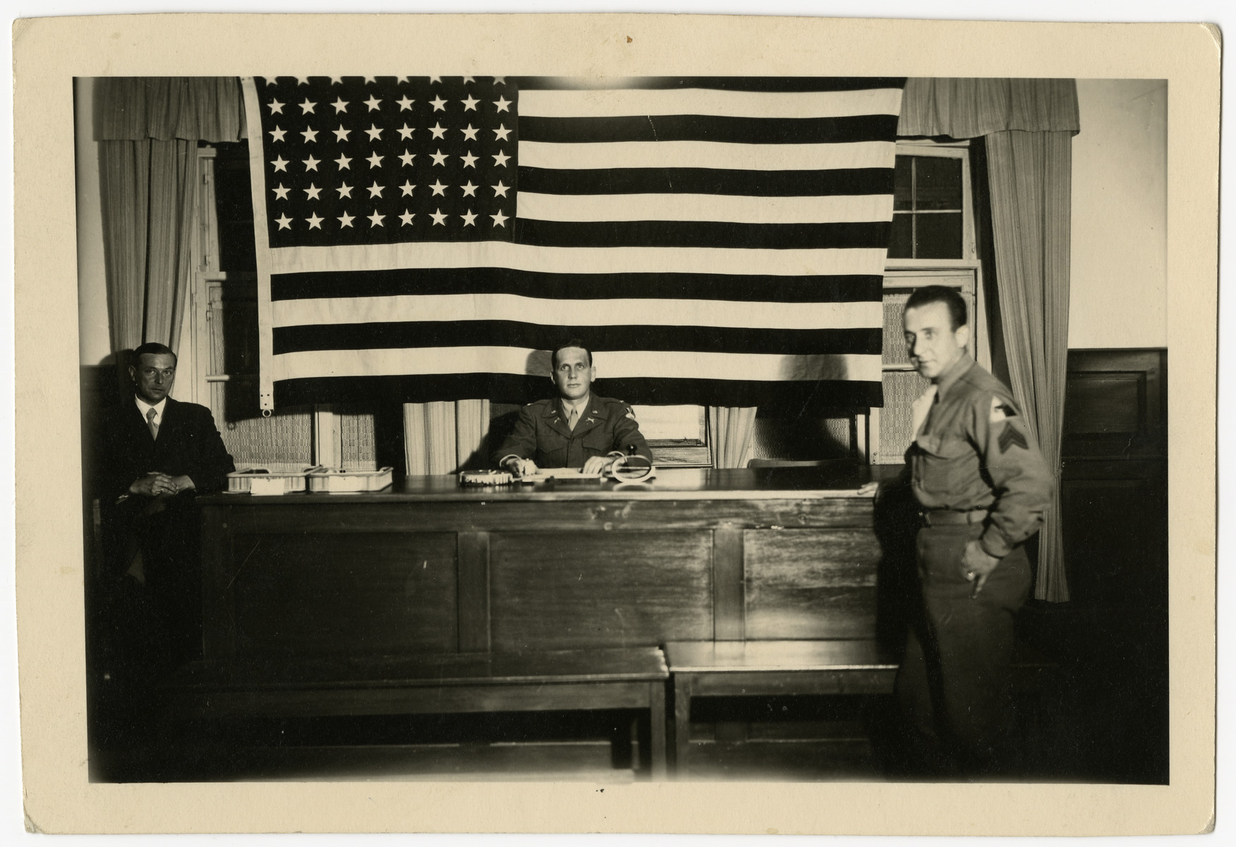 Jacob Postman, a Viennese Jewish emigre, serves as a  translator for the U.S. Army in an unidentified war crimes trial.    Jacob Postman is standing on the far right.  Lt. Kizer is sitting at the desk in front of the flag.