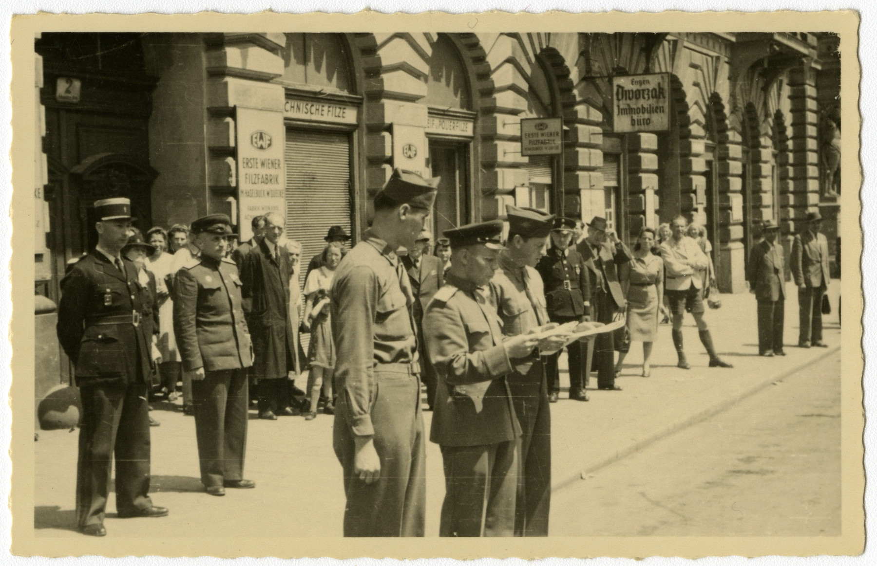 Members of the Four Power International Patrol of Russian, French, British, and American military police gather on a street in Vienna.