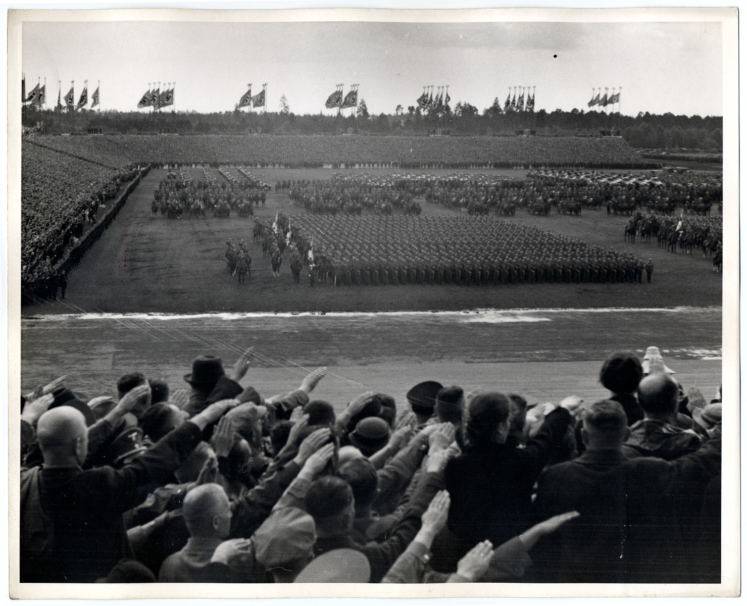 German soldiers, some on horse back, stand at attention in front of saluting spectators during war games at the Nazi Party Congress in Nuremberg.