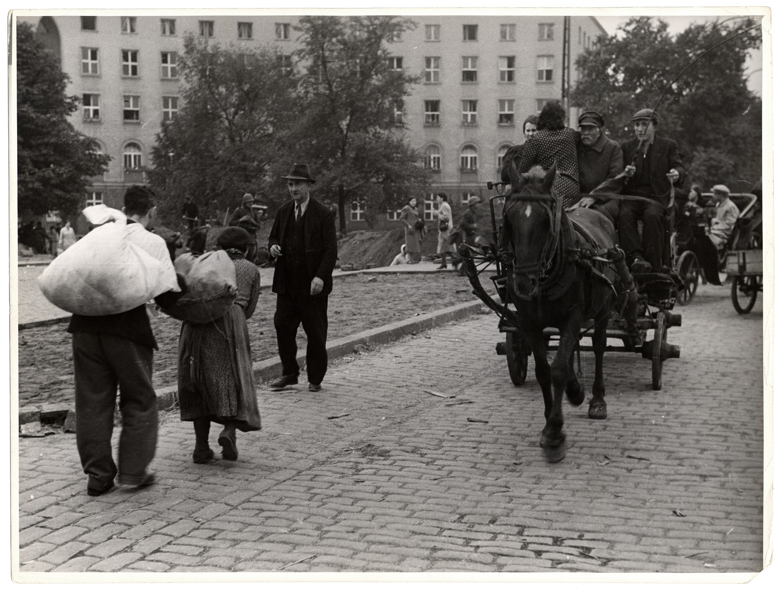 Polish civilians carry bundles and travel in horse-drawn carriages during the siege of Warsaw.