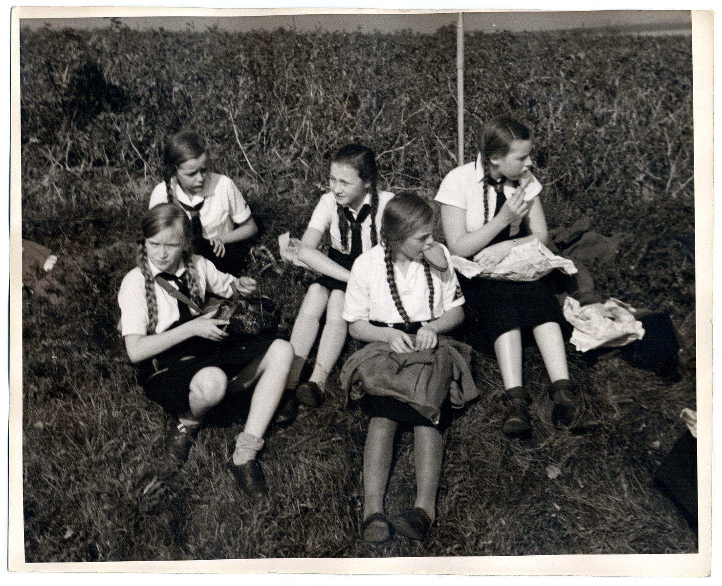 Members of the League of German Girls have a meal on a lawn.