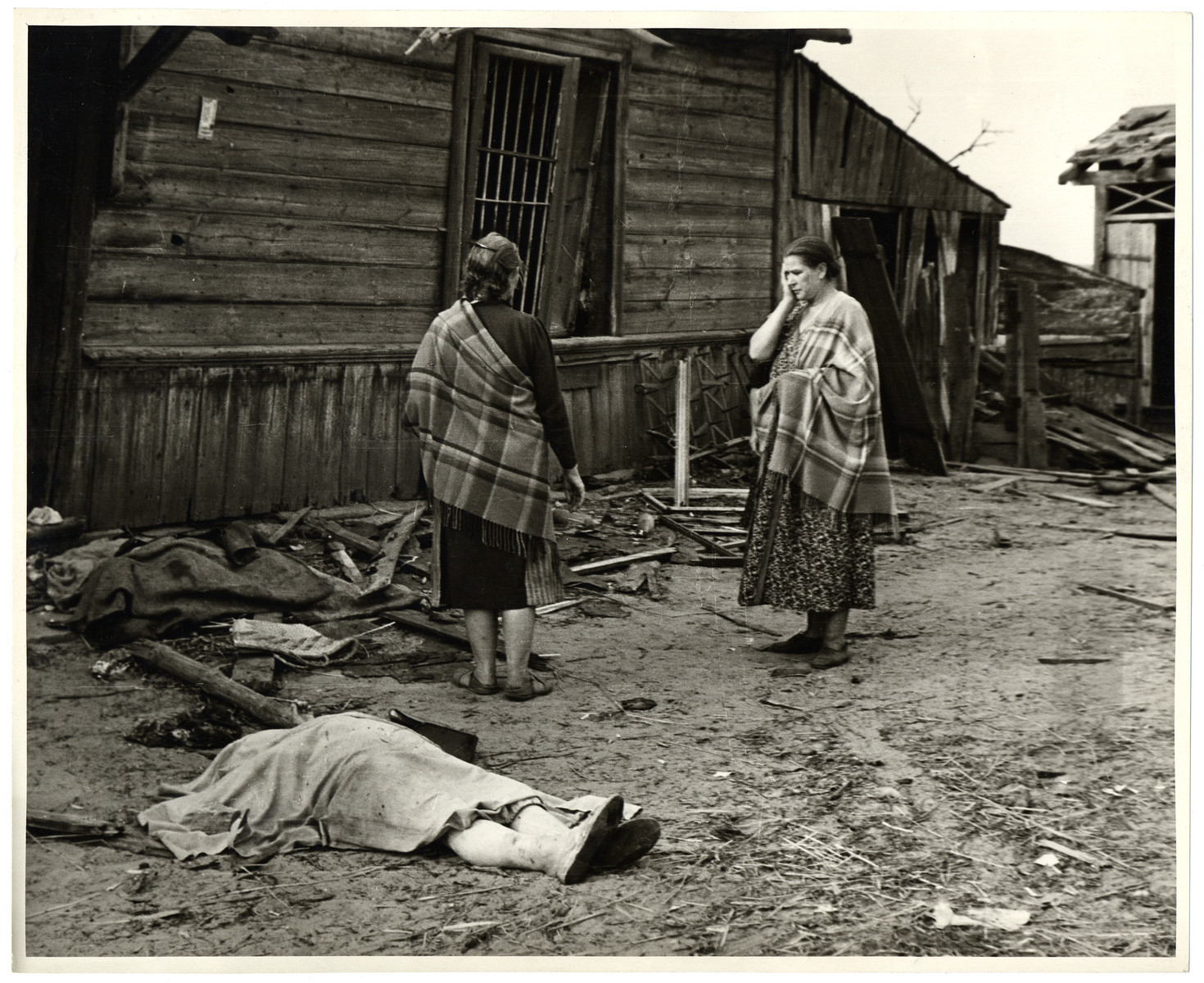 Two Polish women stand horrified after the destruction of their homes by the Germans - in the foreground is the corpse of one of the women killed in the air raid.