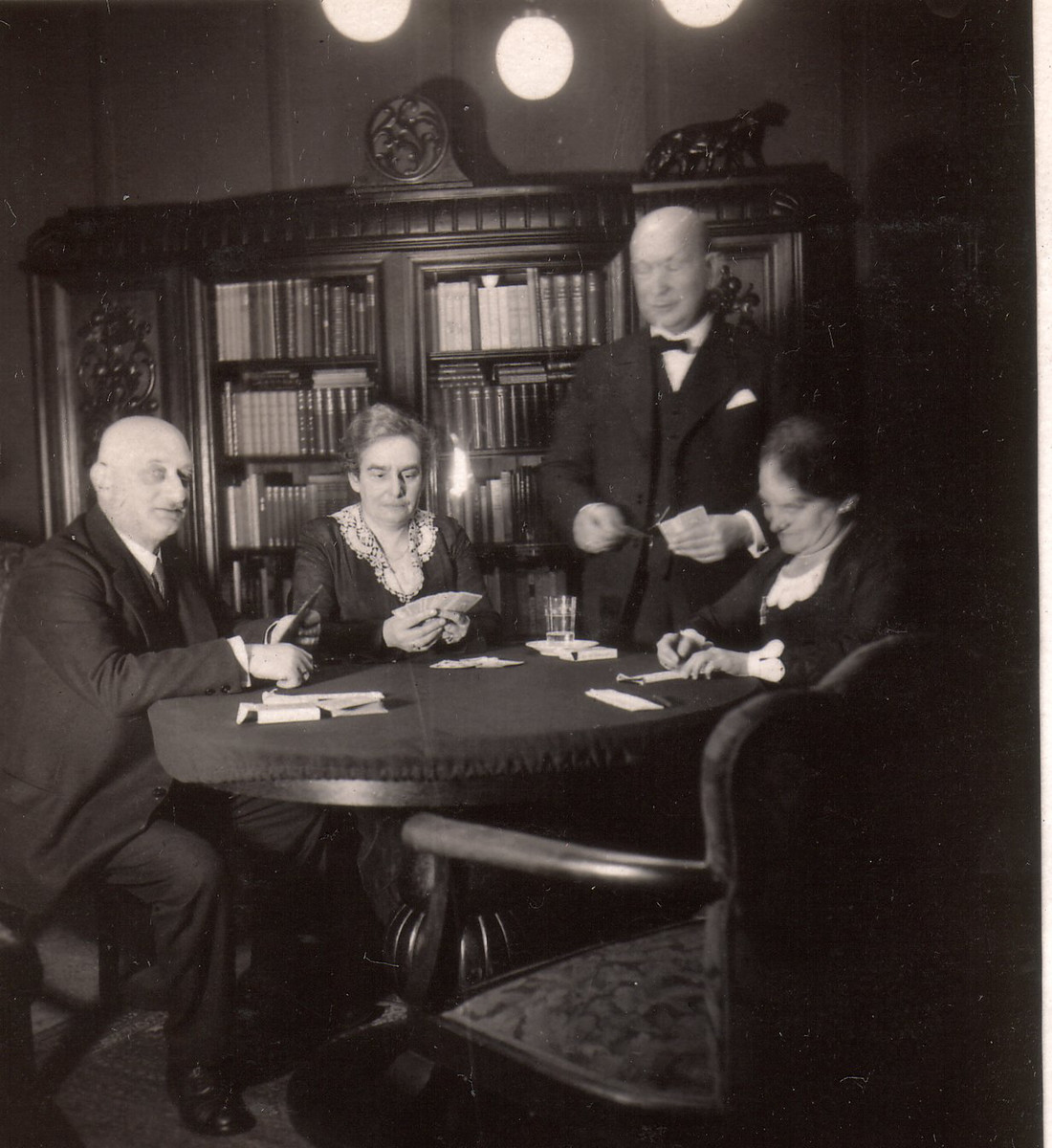 At home in the Weinlaub's parlor in Hannover, two Jewish families get together for bridge .  Seated left to right are Luis Rehfisch, Gertrude Weinlaub and Bertha Rehfisch. Adolph Weinlaub is standing behind Bertha.