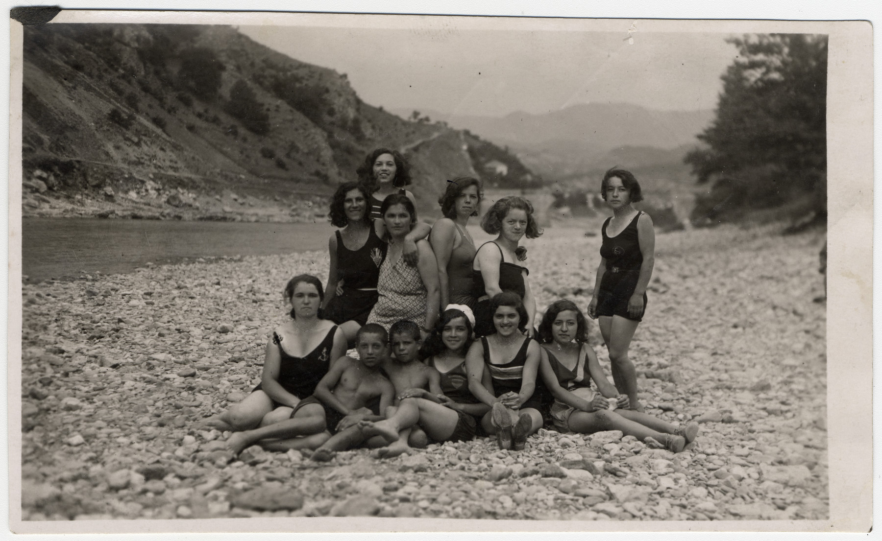 Several young women and two boys pose  on a rocky beach by the Drina River.   Klara, Simha, and Flora Papo are pictured seated first through third from the right.  Hana Levi is the second from the right in the back row.