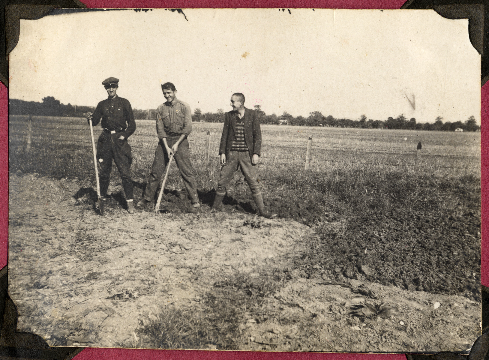 Three unidentified young men pose with farm tools in an unidentified field.