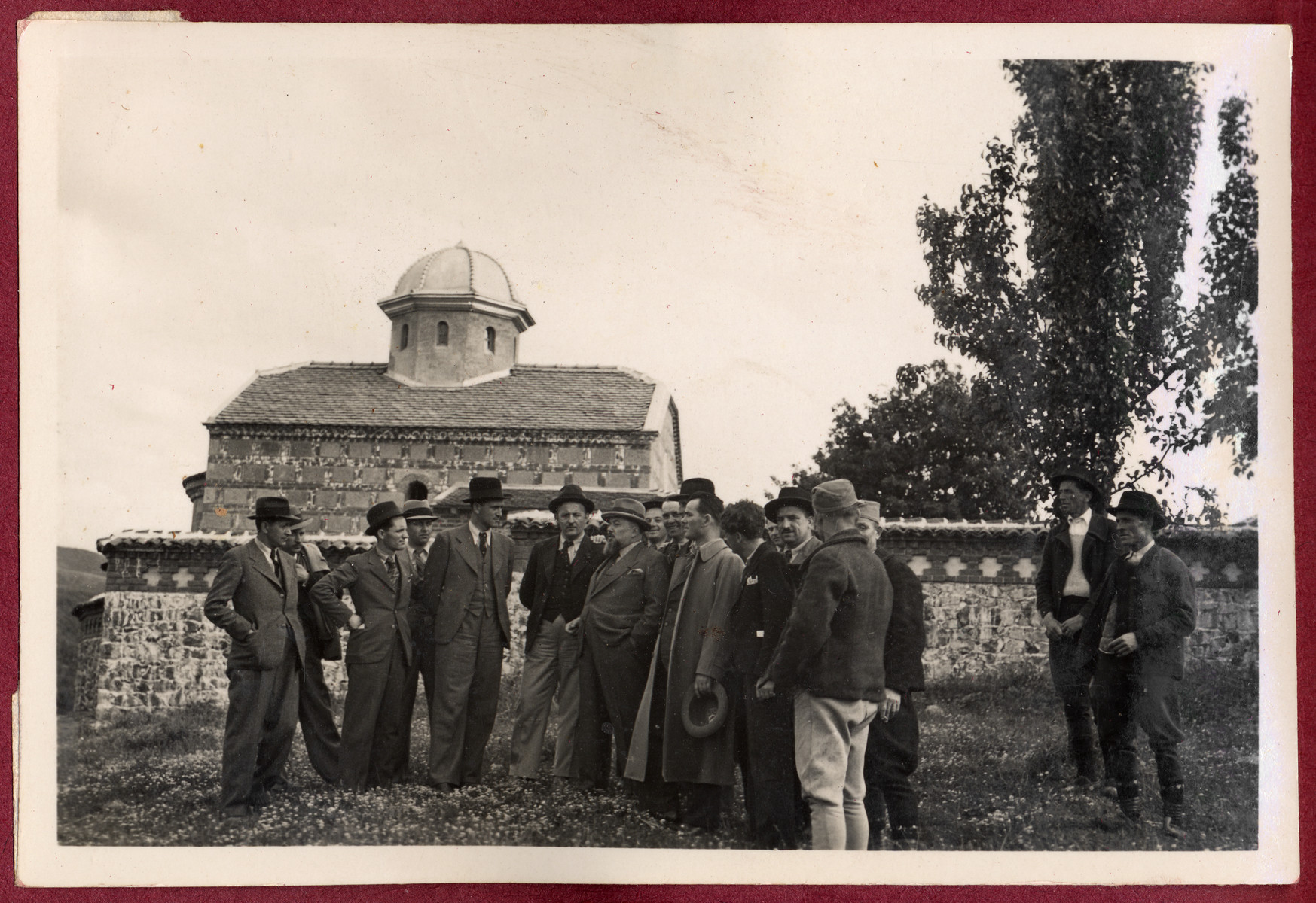 Jevrem Dragojevic poses with others before the wall of church.