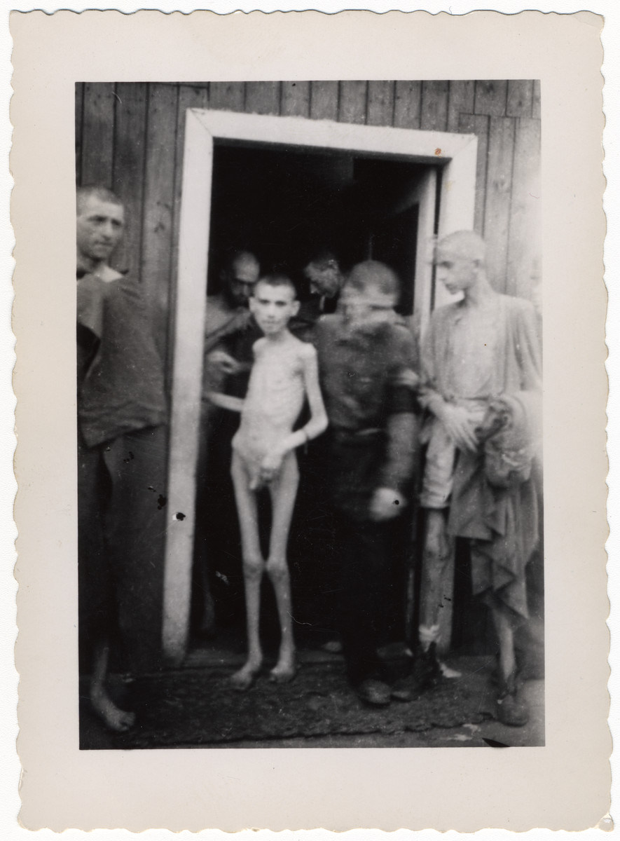 Survivors, some undressed, stand by a barrack door after liberation.