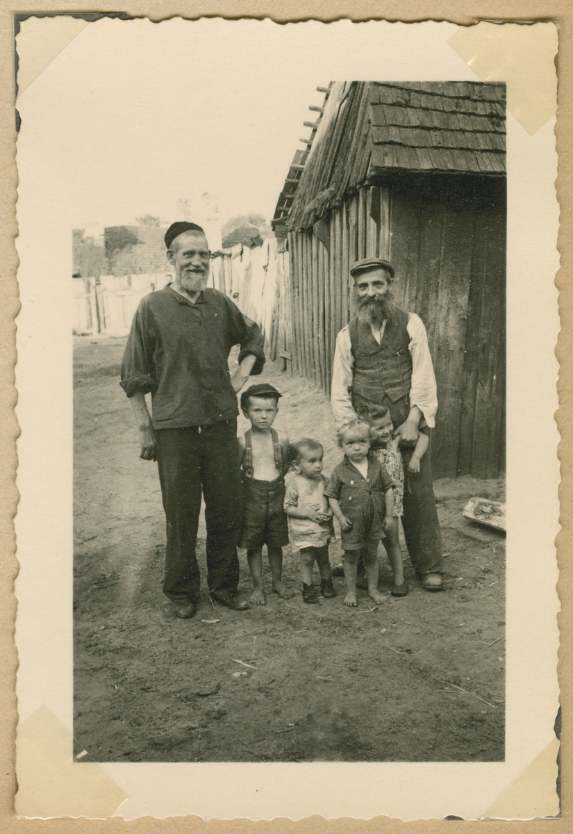 Two religious Jewish men pose with young children in Deblin-Irena.