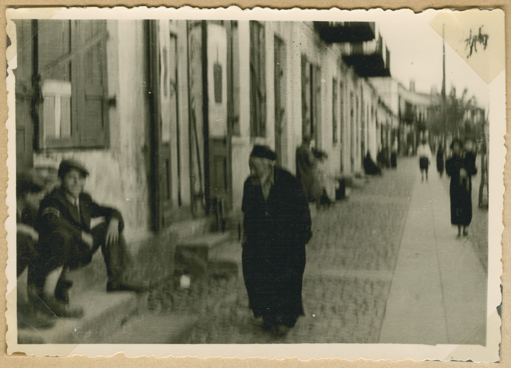 Jews sit on doorsteps and walk down a street of what probably is the Deblin-Irena ghetto.