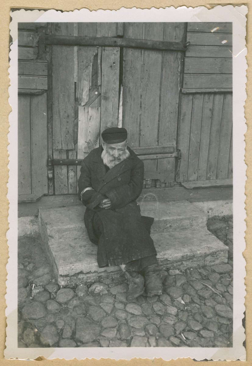 An elderly Jewish man wearing an armband sits on the stoop of a building in Deblin-Irena.