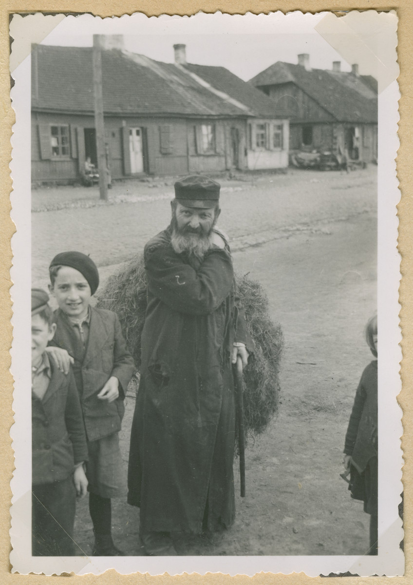 A Jewish man carries hay on his back in Deblin-Irena.