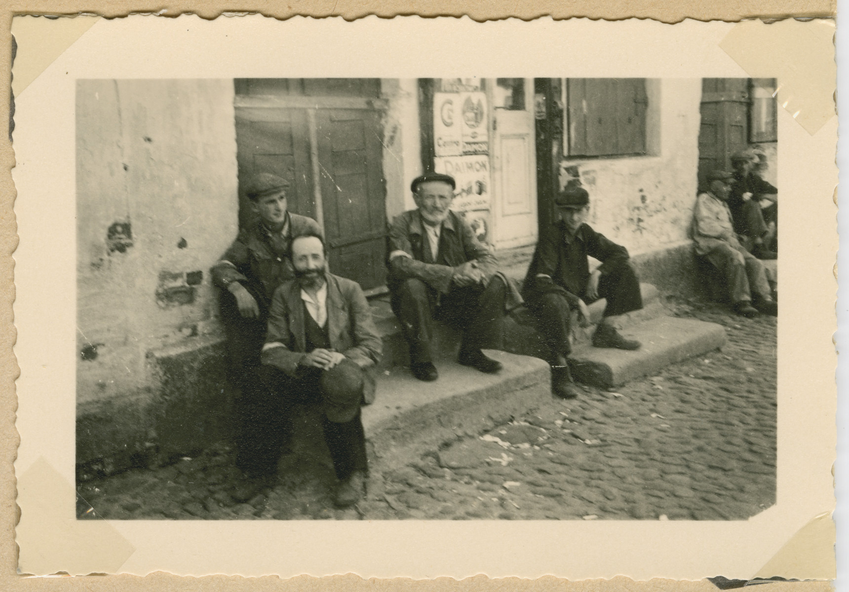 A group of Jewish men wearing armbands sits on the stoop of a building in Deblin-Irena