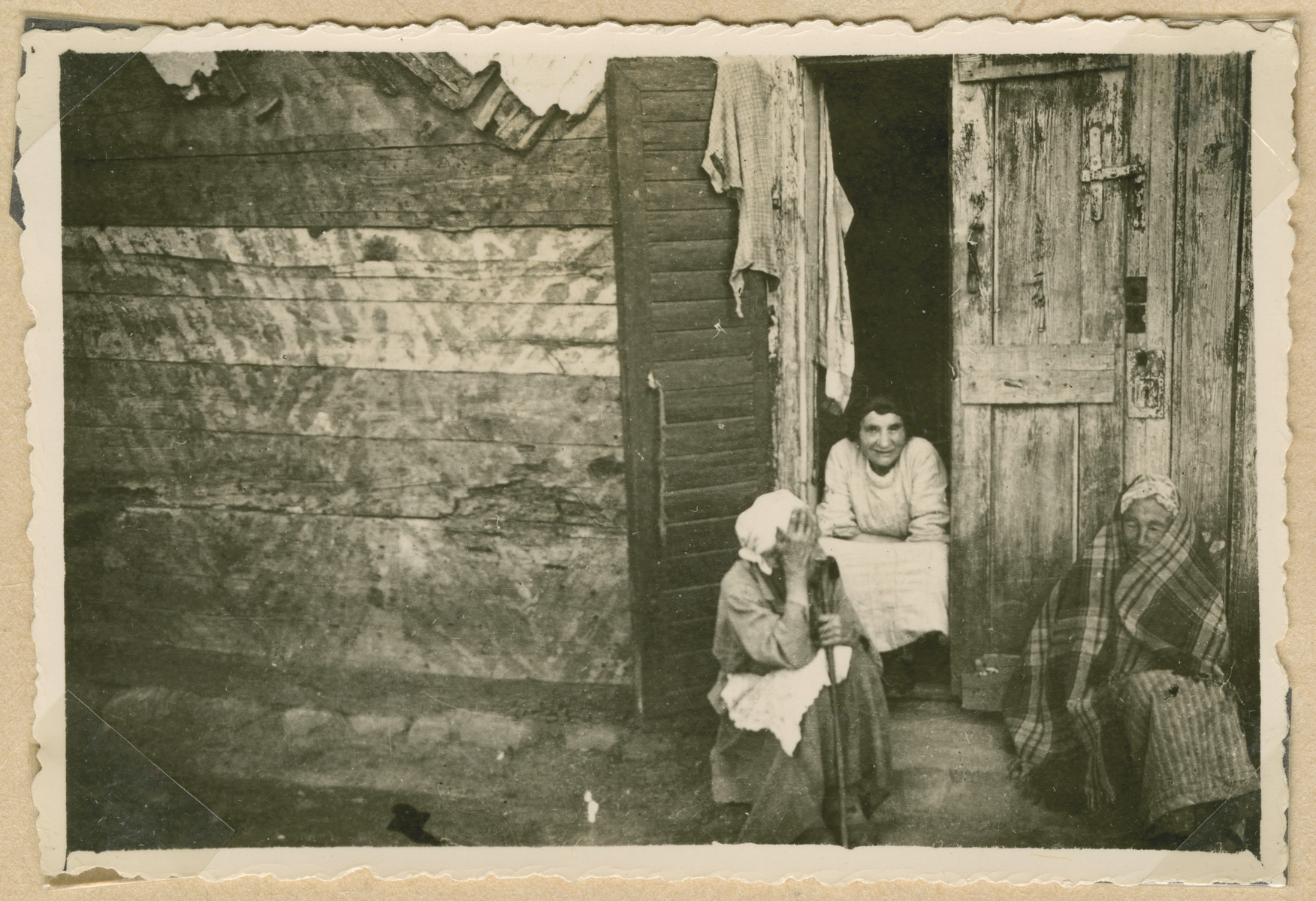 Three women gather on a stoop outside a dilapidated home in Deblin-Irena.