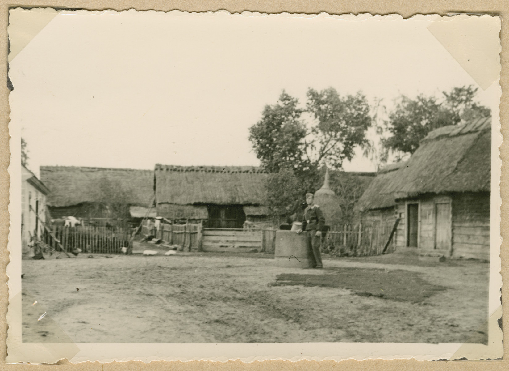 A German soldier stands outside buildings with thatched roofs in Irena.
