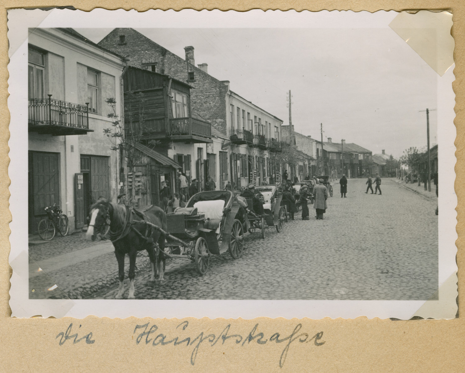 "Horse and carriages are parked on Ulica Okólna in Deblin, Poland.  The original caption reads: ""The main street."""
