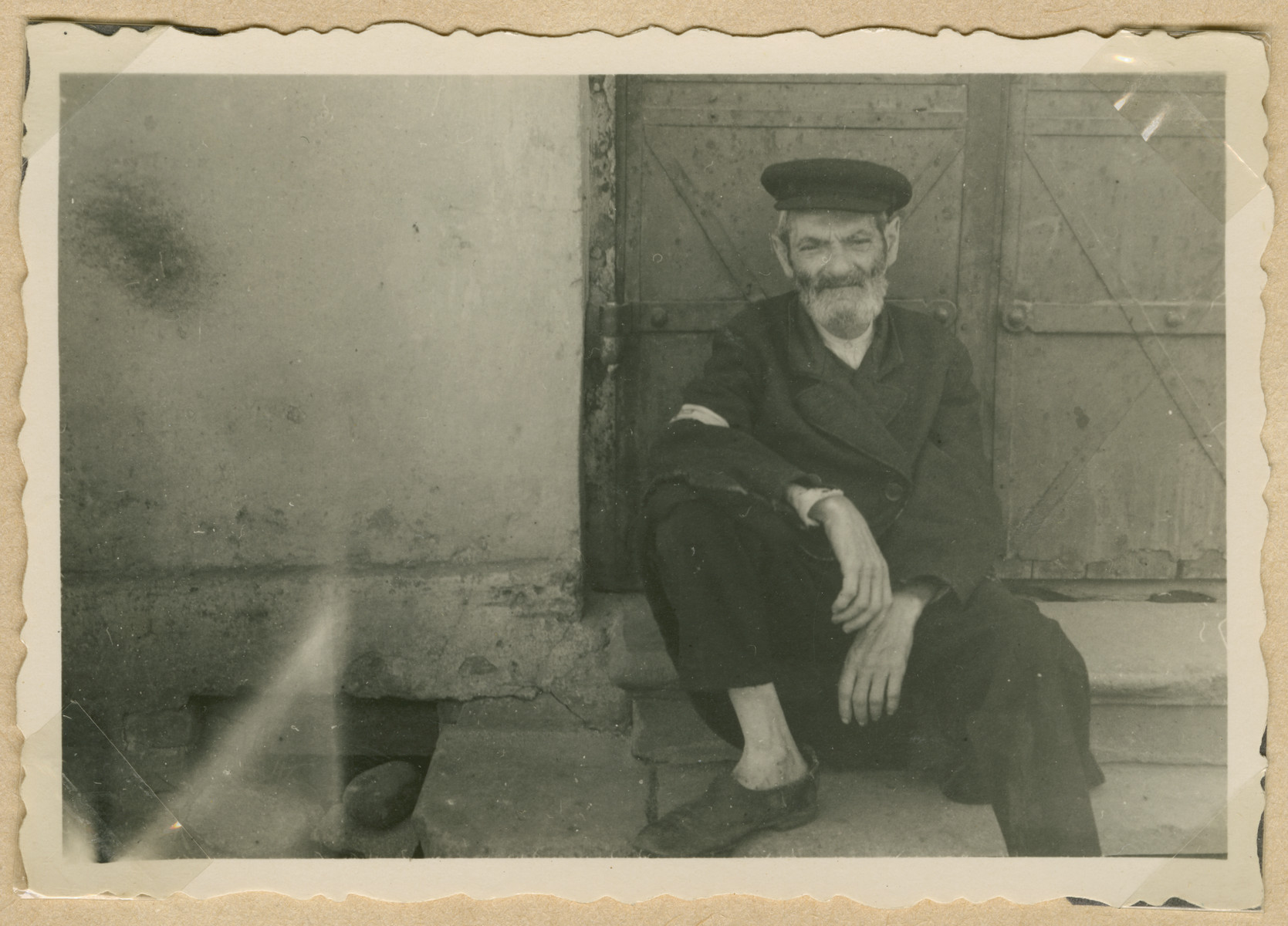 Close-up view of a bearded man sitting on a doorstep in what probably is the Deblin-Irena ghetto.