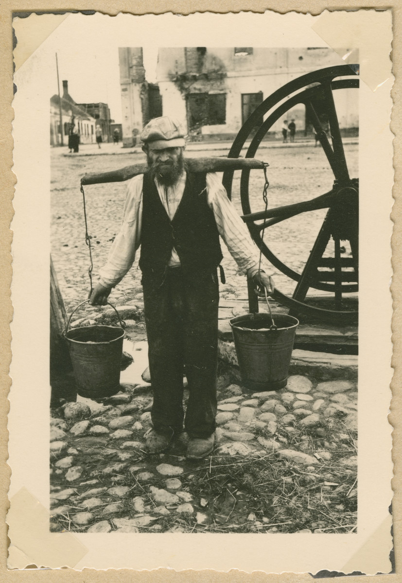 A Jewish man carries water buckets balanced on his shoulders.