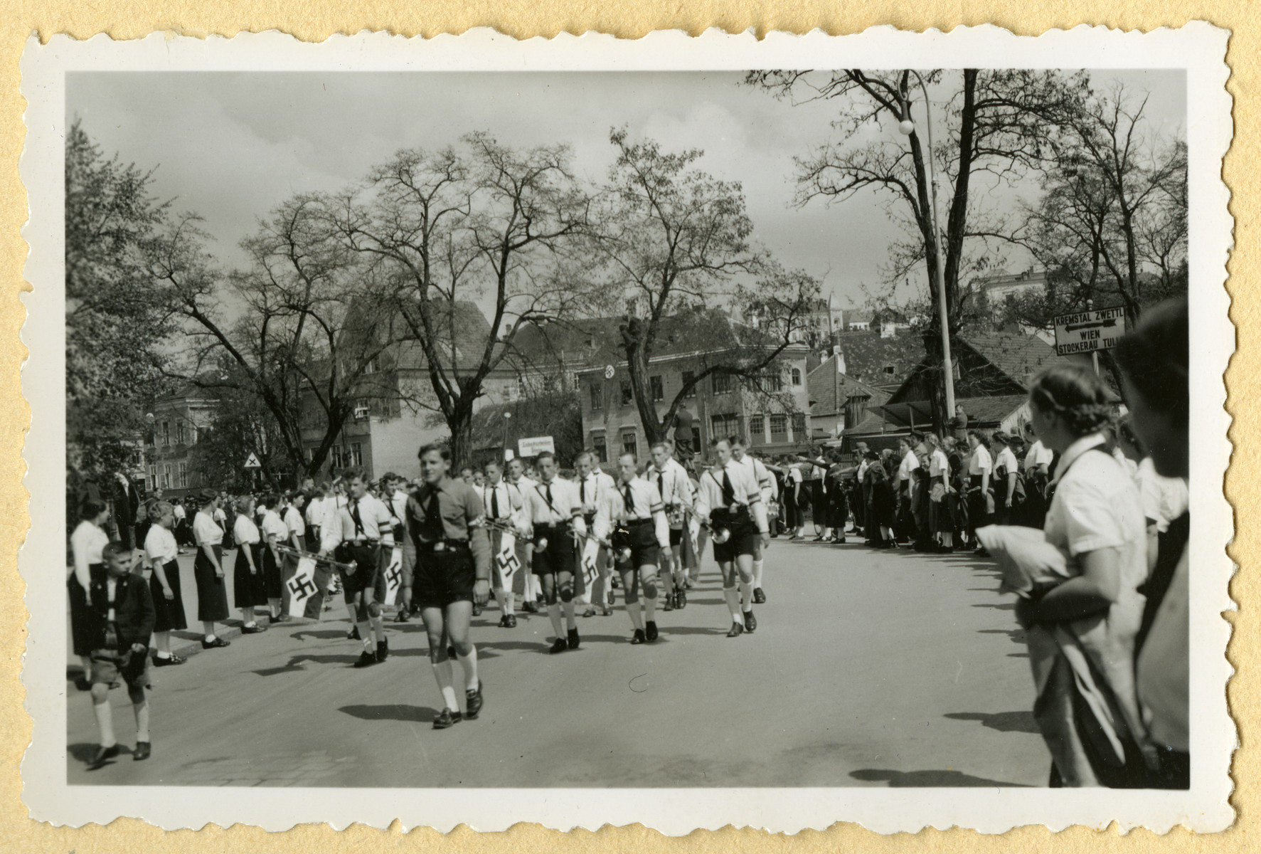 Hitler Youth march through an unidentified German city while members of the League of Geman Girls look on.