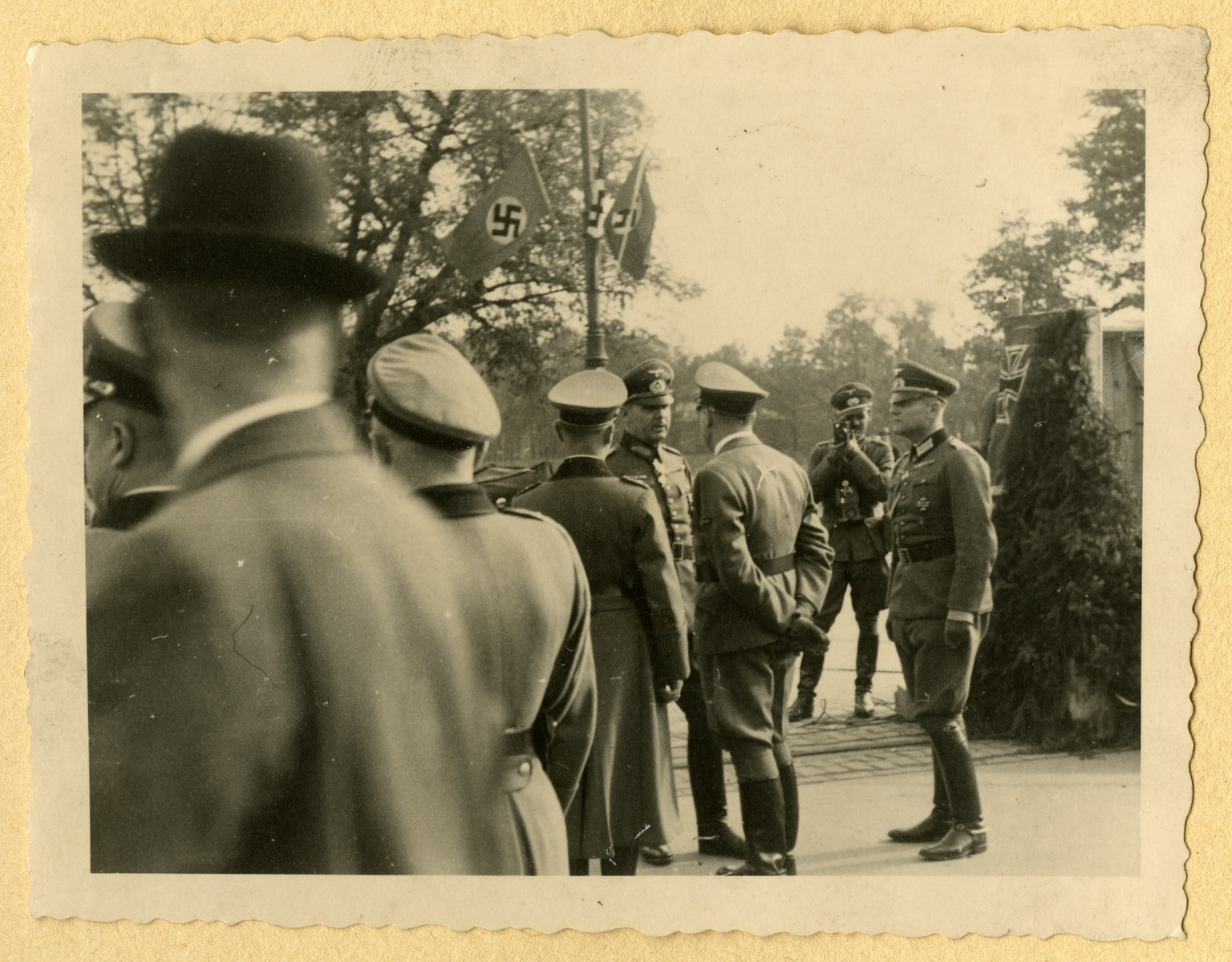 German officers gather for a meeting at an unidentified locale; one takes photographs of the event.