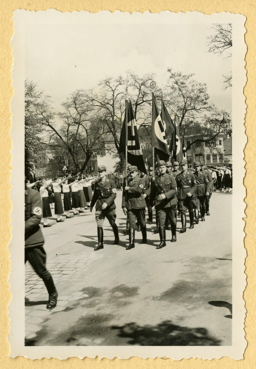 Nazis carrying flags march down a street while members of the League of German Girls stand on the sidewalk salute.