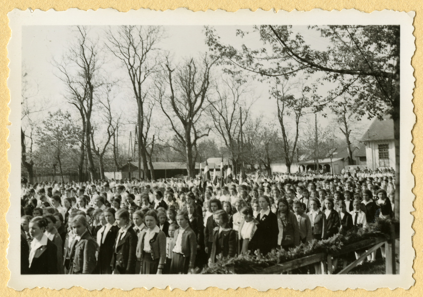 German girls stand at attention at a large outdoor gathering.