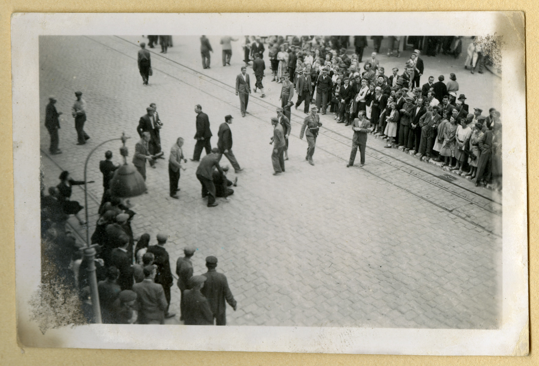 Bystanders watch Jews as they are rounded up and attacked on a street in Lvov.