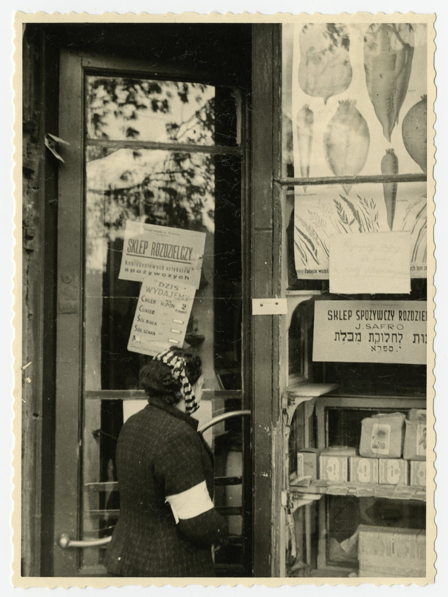 A Jewish woman wearing an armband looks at a grocery shop window in the Warsaw ghetto.