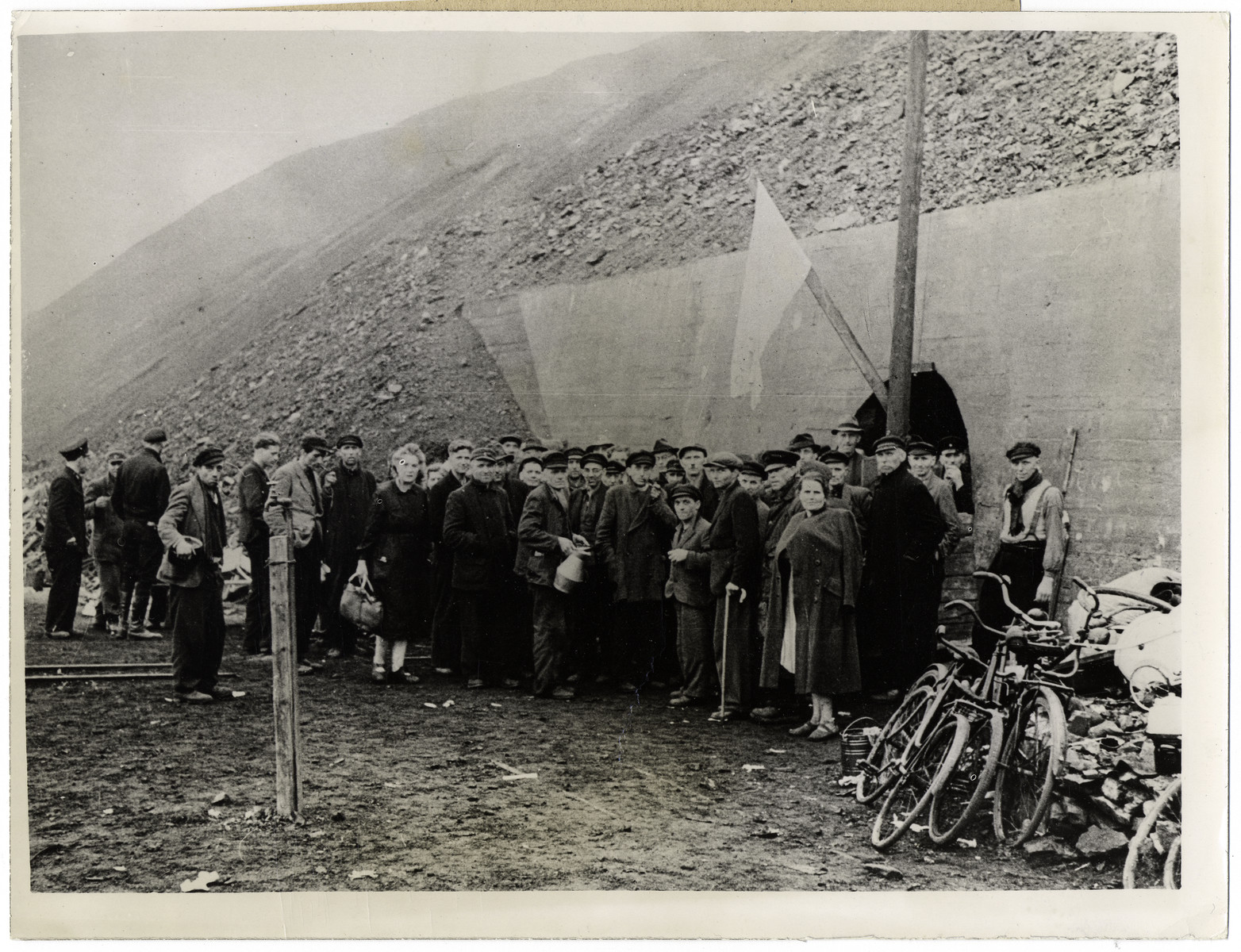 "A group of the civilians who had been living in a mine stand under a white flag of surrender after arrival of Ninth U.S. Army troops.  Original Caption: ""About 7,000 German civilians recently surrendered to Ninth U.S. Army troops after going with little food or water for four days in a shelter in the shafts of a mine slagpile in the Ninth Army sector east of the Rhine River, Germany. Previously, when they attempted to hoist the white flag, Nazi troops fired into their  midst with machine guns."""