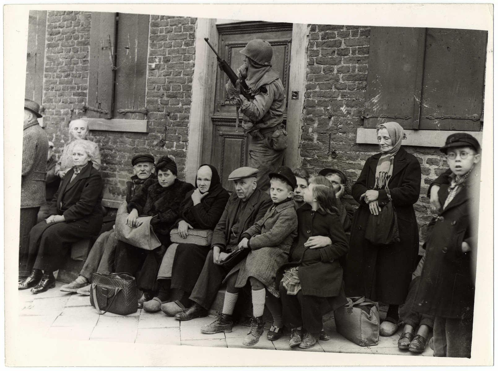 "Original Caption: ""German civilians sit with their children outside of a house in a Reich town captured by the troops of the Ninth U.S. Army advancing to the Rhine River. The civilians have been lined up for questioning by an American officer. units of the Ninth Army reached the Rhine March 2, 1945, when they captured Neuss opposite the industrial center of Dusseldorf."""