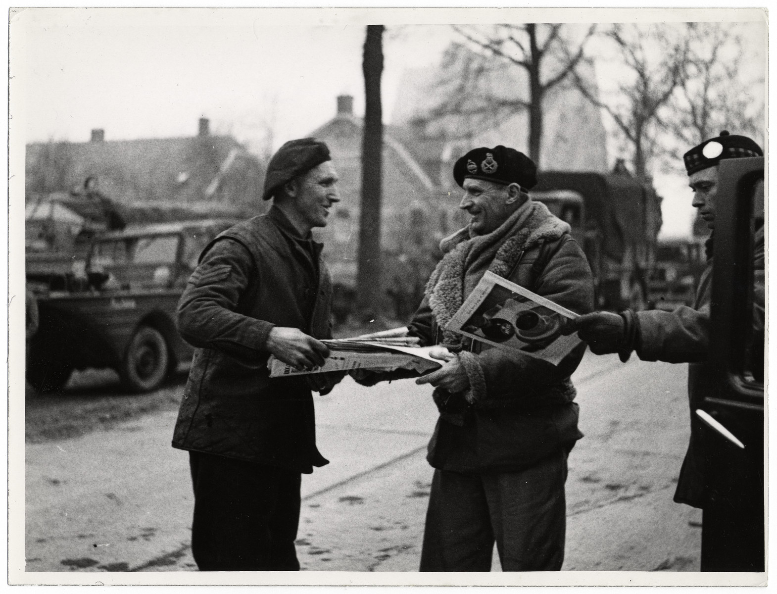 "Field Marshal Bernard Montgomery visits British troops in Germany.  Original Caption: ""Field Marshal Sir Bernard L. Montgomery has visited the British troops in the Cleve area, Germany. He arrived in a Dukw amphibious lorry. He took with him magazines, newspapers and cigarettes for the men.""  This picture shows: On his return journey, the Field Marshal stops and gives some books to Sergeant Snelling (s outhall) R.A.S.C."""