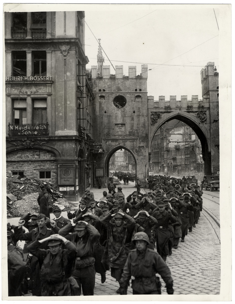"German soldiers march through a street in Munich after their surrender and capture.  Original Caption: ""Munich has fallen, Hitler's sacred city, the scene of the abortive putsch of 1923, the cradle of Nazism is now watching Europe's evil child being thrown finally intoo its grave. The men of general Patch's Seventh US Army marching through the city can see the beer cellar and the Draunhaus, so recently the supreme symbols of Hitler's black regime, now battered relics of a madman's dream of power."""
