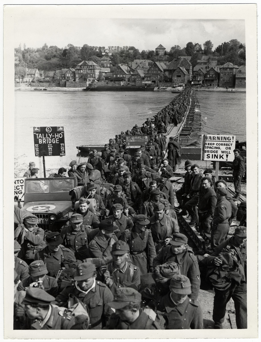 "German soldiers cross the Elbe River as they surrender to British forces.  Among those pictured (to the right of the sign) is  Lance Corporal William Charles Brind, 53rd Welsh Regiment (previously  Royal Berkshire Regiment).  He served in the BEF and was evacuated from Dunkirk in 1940.    Original Caption: ""Thousands of men crossing the river Elbe there were no British quards in sight - they weren't necessary. Prisoners came from many miles to the East."""