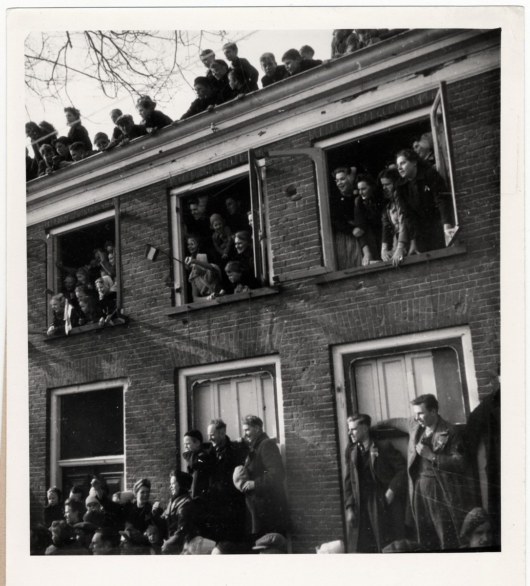 """Men, women and children crowd the windows of their homes in Domburn on Walcheren Island to see and welcome Queen Wilhelmina.  Original Caption: """"In her first visit to her country after five years of exile, Queen Wilhelmina cisted every town, every village and every hamlet that she could fit into a 10-day tour of liberated areas in Hlooand. The 65-year-old Queen did not spare herself. She saw the vast stretches of inundated countryside, which will remain barren for years to come even after the bombed dikes of The Netherlands are repaired. She saw the depris of towns where fighting took place only a few days before her visit, gave sympathy and solace to men, woman and children who were wounded or bereaved. She met the valiant miners of Hoerlan and Venlo. Wherever she stopped, she talked with the men and women wo fought stubbornly and silently in the Dutch Resistance Movement. It was announced March 23, 1945, that the unofficial, unplanned tour had ended with queen Wilhelmina's return to England. The queen was born in the Hague in 1880 and has reigned on the Dutch throne since 1890. When the Germans invaded Holland in May, 1940, Queen Wilhelmina was forced to flee to England."""""""