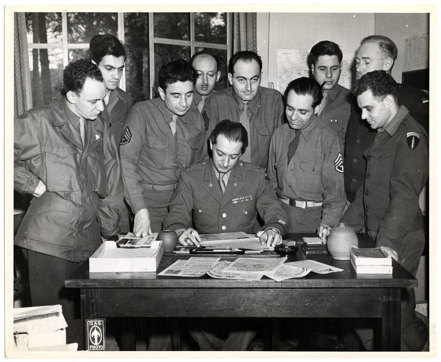 Members of the 4th Communications Unit, a counter-intelligence unit, study the German newspapers it was responsible for publishing.  Almost all the members were naturalized Americans, themselves refugees from Nazi Germany.    Among those pictured are: seated, Hans Habe (born Janos Békessey), and from left to right,  unknown; Ernest (originally Ernst) Wynder, Konrad Kellen (last name originally Katzenellenbogen, unknown, Stefan Heym (birth name Helmut Flieg), Louis Atlas, Peter Weidenreich (last name later changed to Wyden), unknown, and Joseph Eaton, the donor,  is standing on the far right.