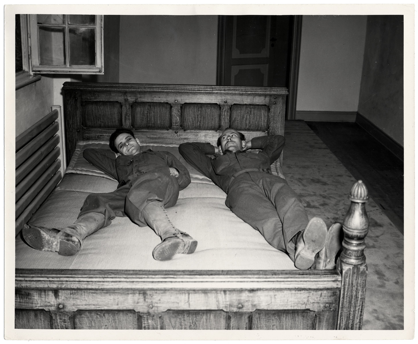 Sgt. Everett Steiger from Salem, Oregon and T/4 Joseph W. Eaton relax on the bed that had belonged to Joseph Goebbels at Schloss Rheydt.   It was moved into the hallway by the GI's who are now billeted in the castle and need his room.