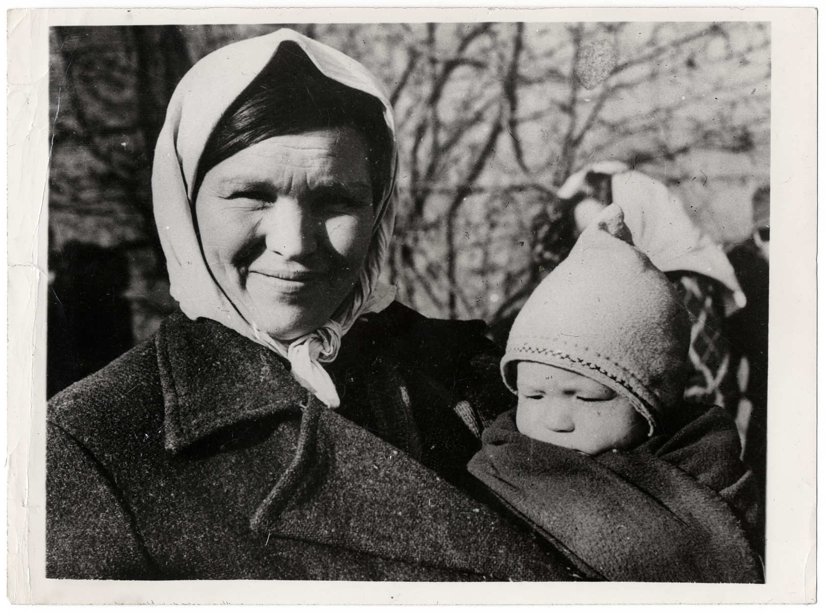 "Close-up portrait of a Russian woman and infant awaiting repatriation.  Original Caption: ""As Allied armies on the Western Front sweep eastward across the Reich, they are freeing tens of thousands of foreign workers from Nazi slave labor camps. These displaced persons are temporarily placed in repatiation camps until they can be transported to their homelands by the Allies. At the camps, they are carefully questioned to make sure they are not German soldiers disguised as civilians. At one displaced persons center, 28 out of 3,000 men proved to be German troops attempting to flee into Belgium and Holland.  By March 19, 1945, freed French slave workers were arriving in Paris at the rate of 2,000 daily and it was estimated that approximately 2,500,000 French nationals were still inside Germany. Estimates of the total number of foreign workers in the Reich run as high as 20,000,000, most of them being Russians or Poles. U.S. General of the Army Dwight D. Eisenhower, Supreme Commander-in-Cheif Allied Expoditionary Force has requested the United Nations relief and Rehibilitation Administration to train between 3,500 and 6,000 persons to operate assembly centers, and 21 UNRRA teams had arrived in Europe by March 31.  These pictures show a few of the 5,000 displaced persons registered at a single repatiation camp on the Western Front during 12 days. ""  This Photo Shows: A smiling Russian woman and her child await transportation for the frist part of the long journey home from the Reich. At one slave camp liberated by U.S. troops, Russian girls told their liberators they worked 12 hours a day in a factory and were beaten if they could not lift heavy bombs."""