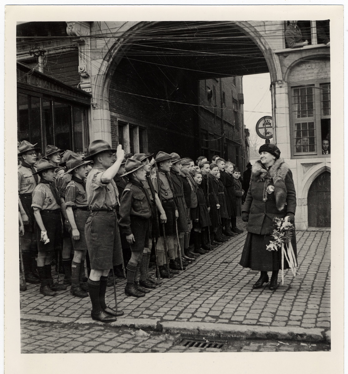 "Queen Wilhelmina acknowledges the salute of a troop of Boy Scouts at Bergen op Zoom.  Original Caption: ""In her first visit to her country after five years of exile, Queen Wilhelmina visited every town, every village and every hamlet that she could fit into a 10-day tour of liberated areas in Holland. The 65-year-old Queen did not spare herself. She saw the vast stretches of inundated countryside, which will remain barren for years to come even after the bombed dikes of The Netherlands are repaired. She saw the debris of towns where fighting took place only a few days before her visit, gave sympathy and solace to men, women and children who were wounded or bereaved. She met the valiant miners of Hoerlan and Venlo. Wherever she stopped, she talked with the men and women who fought stubbornly and silently in the Dutch Resistance Movement. It was announced March 23, 1945, that the unofficial, unplanned tour had ended with Queen Wilhelmina's return to England. The queen was born in the Hague in 1880 and has reigned on the Dutch throne since 1890. When the Germans invaded Holland in May, 1940, Queen Wilhelmina was forced to flee to England."""