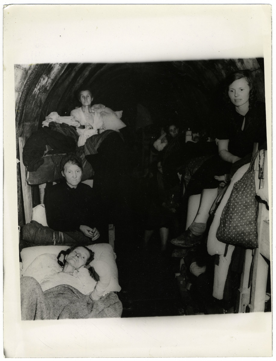 "German women living in primitive dwellings in a mine surrender to American troops.  The original caption reads, ""About 7,000 German civilians recently surrendered to Ninth U.S. Army troops after going with little food or water for four days in a shelter in the shafts of a mine slag pile in the Ninth Army sector east of the Rhine River, Germany. Previously, when they attempted to hoist the white flag, Nazi troops fired into their  midst with machine guns.""  This photo shows: ""German women of the group are pictured inside the primitive dwellings."""