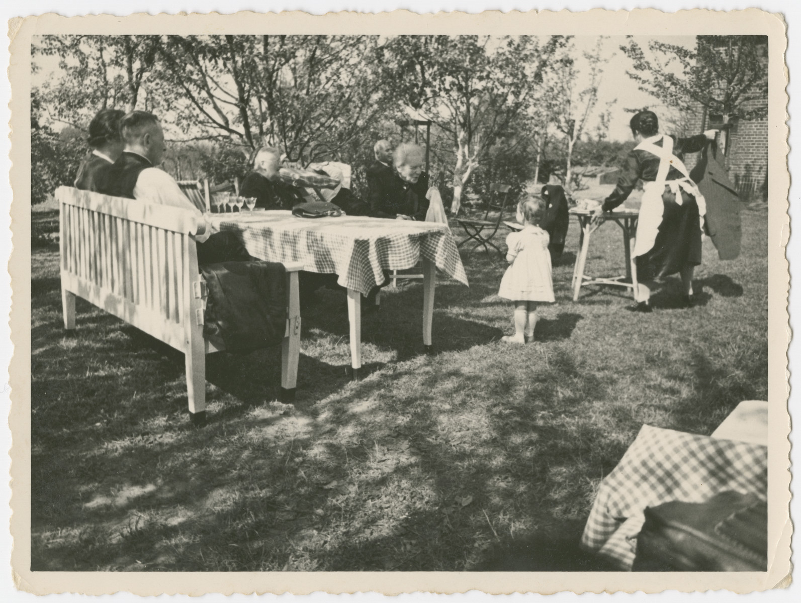 A multi-generational German-Jewish family enjoys a meal outdoors.  Mortiz and Else Gans are pictured on the left with their backs to the camera.  Their mothers are facing them.