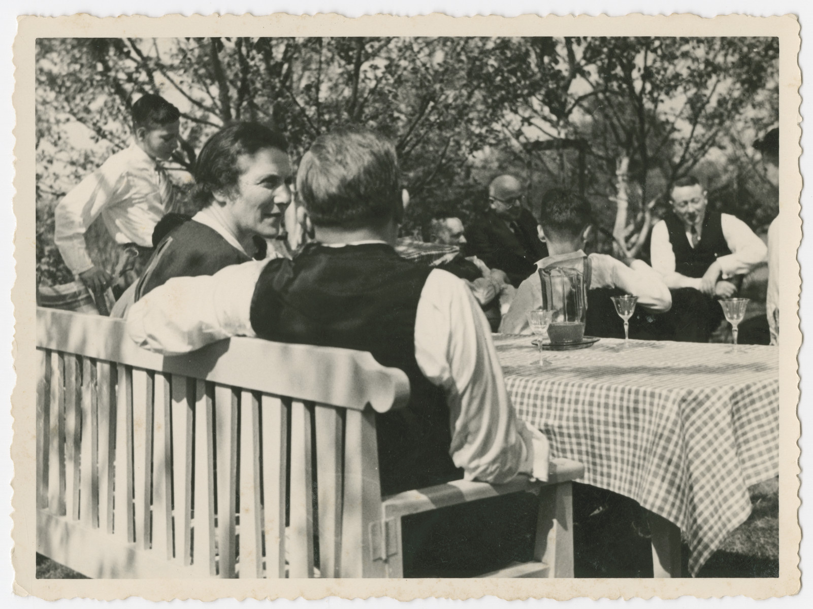 A multi-generational German-Jewish family enjoys a meal outdoors.  Mortiz and Else Gans are pictured on the left with their backs to the camera.  Carl Gans is standing on the far left and Leo Lamm is pictured in he back in the dark suit.  The man to the right of Leo is ,probably his brother Sally.