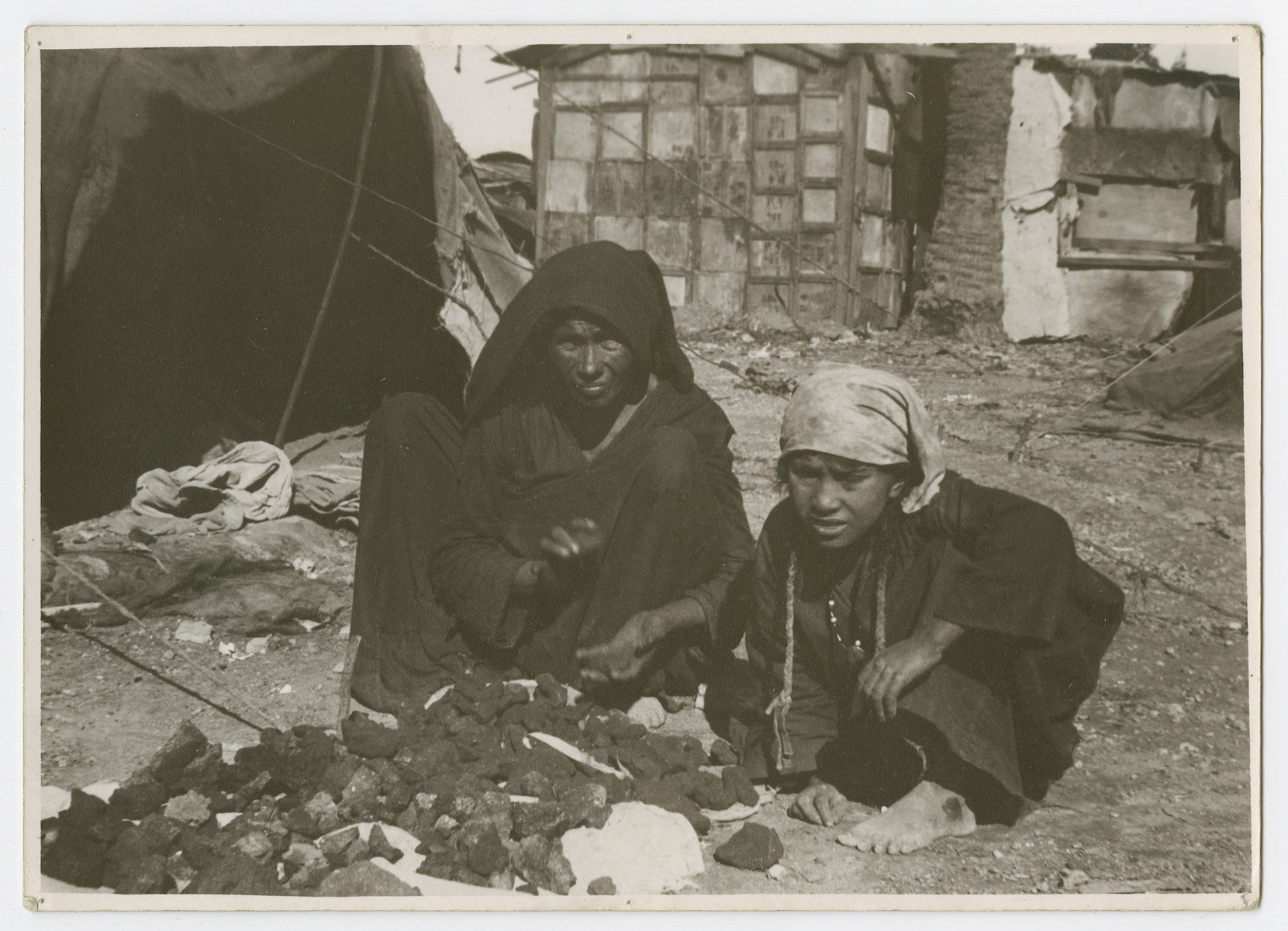 """An Arab or Bedouin woman and child sit by their tent outside a partially destroyed building.  Photograph is used on page 225 of Robert Gessner's """"Some of My Best Friends are Jews."""""""