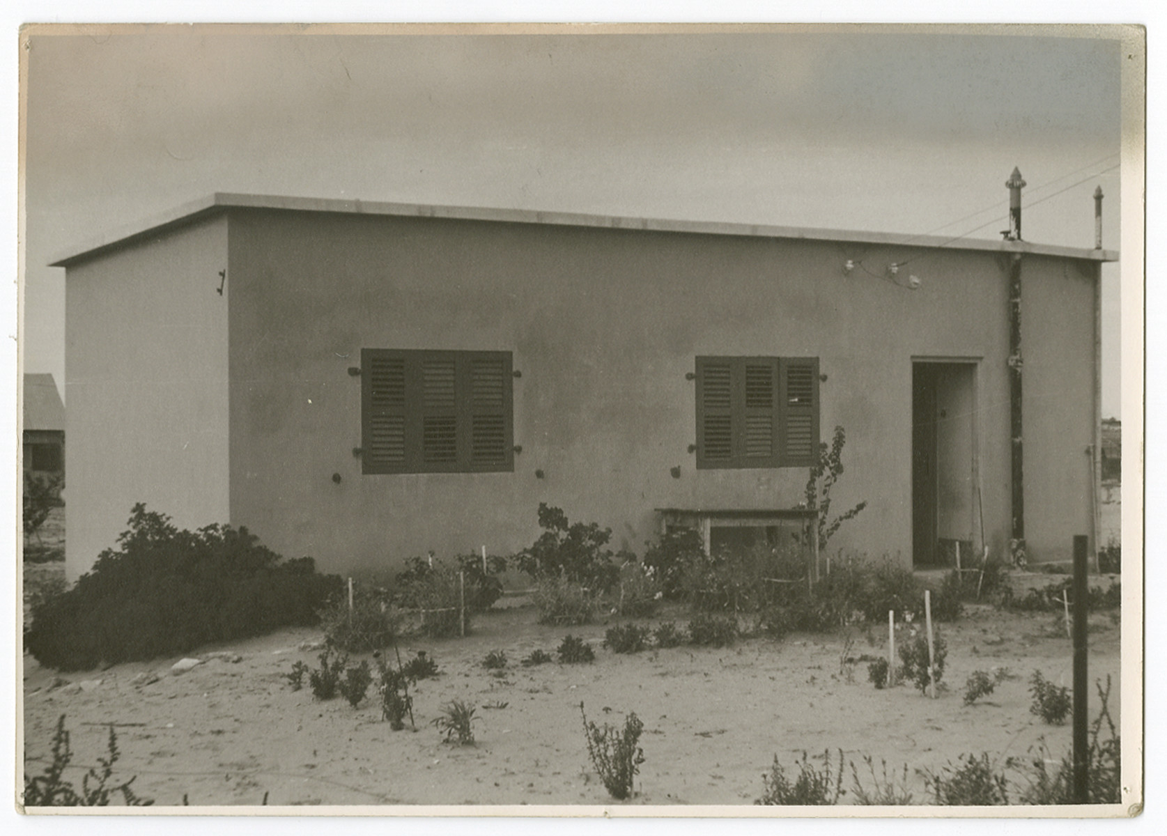"Exterior view of a housing unit in an unidentified settlement in Palestine.  Photograph is used on page 240 of Robert Gessner's ""Some of My Best Friends are Jews."" The pencil inscription on the back of the photograph reads, ""Farmer's home protection ag raids.""   The typed caption attached to the photograph reads, ""Jewish plantation constructed like an American stockade against Arab raids.""a"